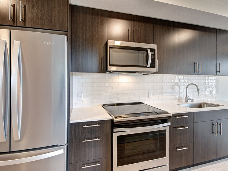 Downtown Seattle WA Apartments-Metroline Flats Apartments Kitchen With Wooden Cabinetry And White Tile Backsplash