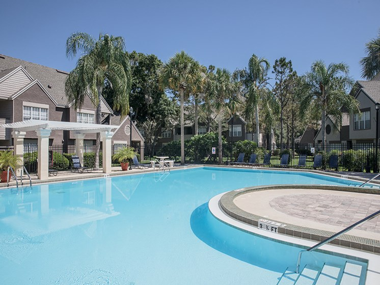 Bloomingdale Woods Apartments Valrico Florida Pool During the Day with view of trees and clubhouse