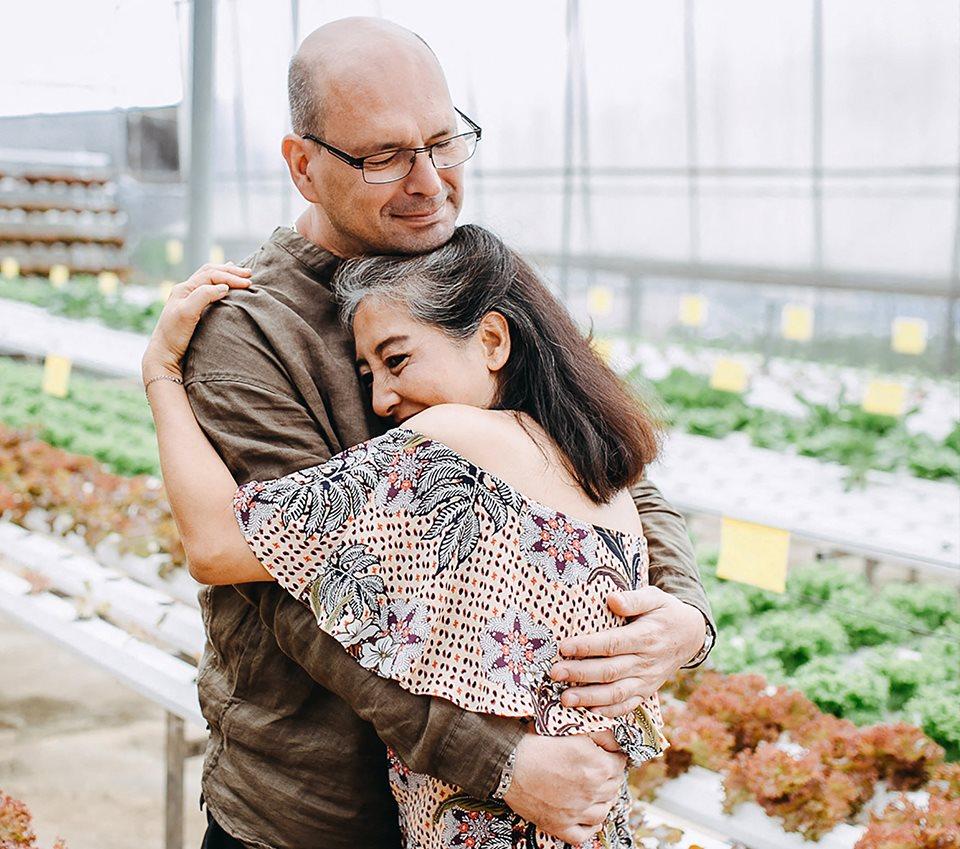 couple hugging near plants