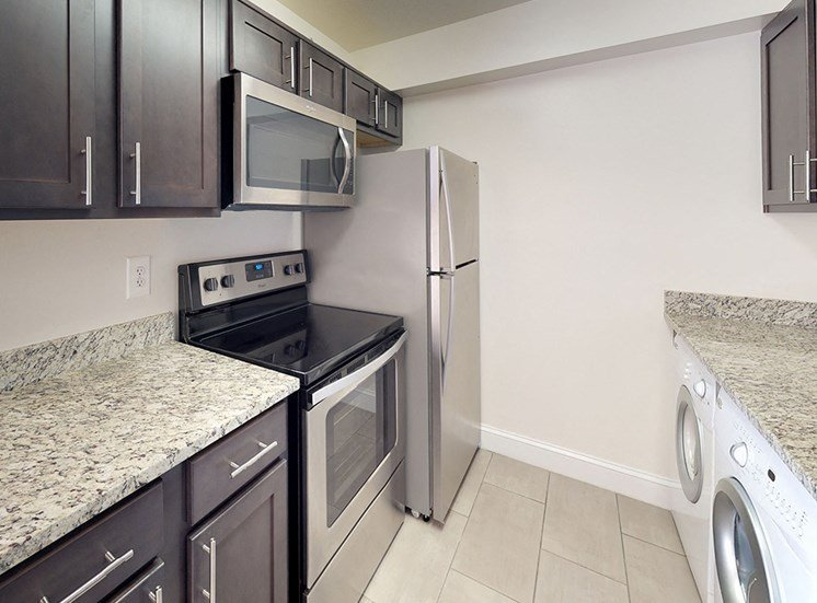 granite countertops and modern appliance inside of apartment unit