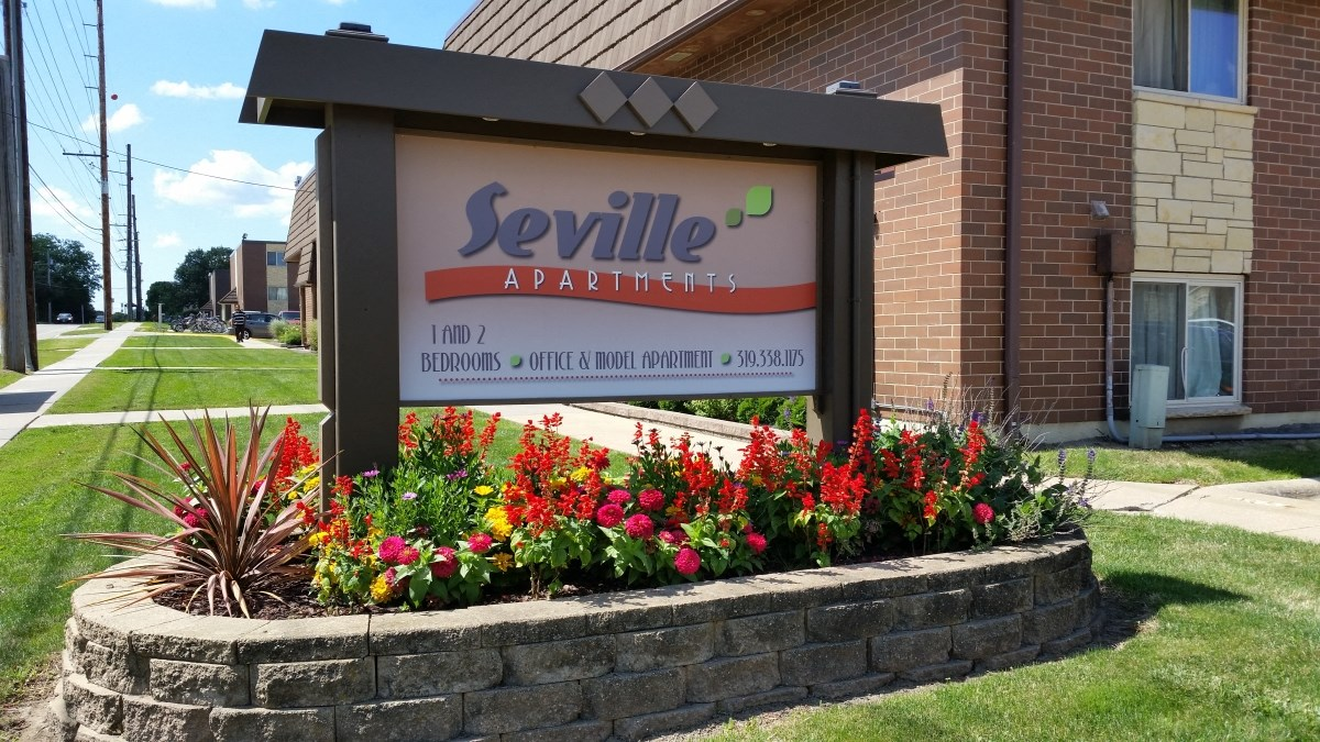 Entrance sign. Nice flower bed at Seville Apartments in Iowa City, IA