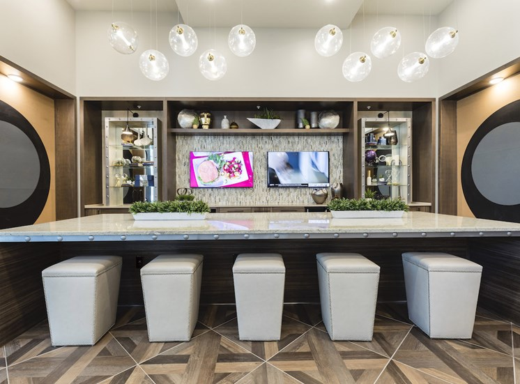 lounge with tvs and bar top with padded stools