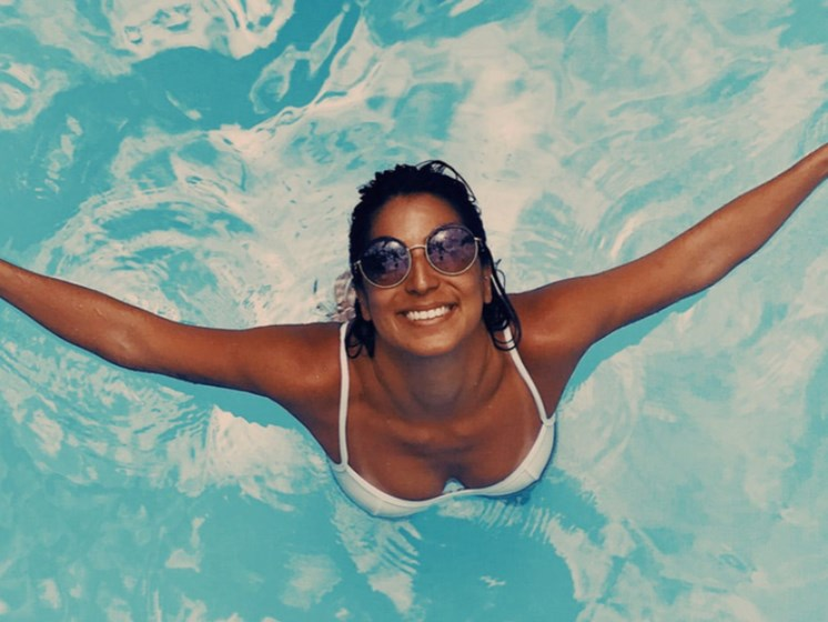 woman enjoying the water in a resort-style swimming pool on-site at 3800 Acqua at Bridgeport Suffolk VA