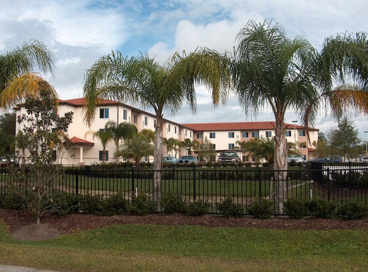 Holy Cross Manor I and II senior apartments in Palmetto, FL  exterior with palm trees