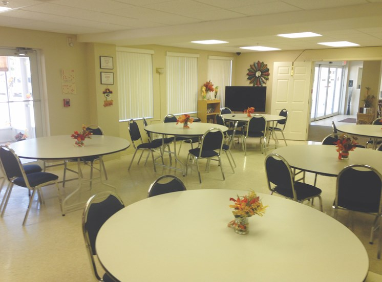 Holy Cross Manor I and II senior apartments in Palmetto, FL community room with tables and chairs