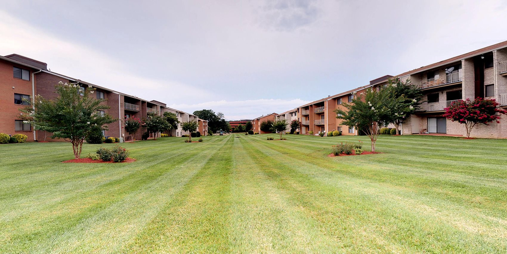large outdoor grass area with exterior view of the apartments