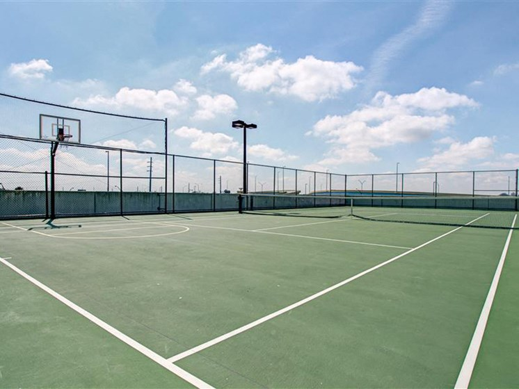 Tennis Court with sunny day and basketball hoop