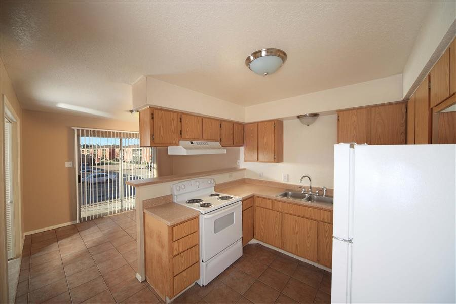 Kitchen with white appliances, stainless steal sink, brown cabinets, and tile like floor. The kitchen is open to the dinning room that opens to the patio with sliding glass doors.