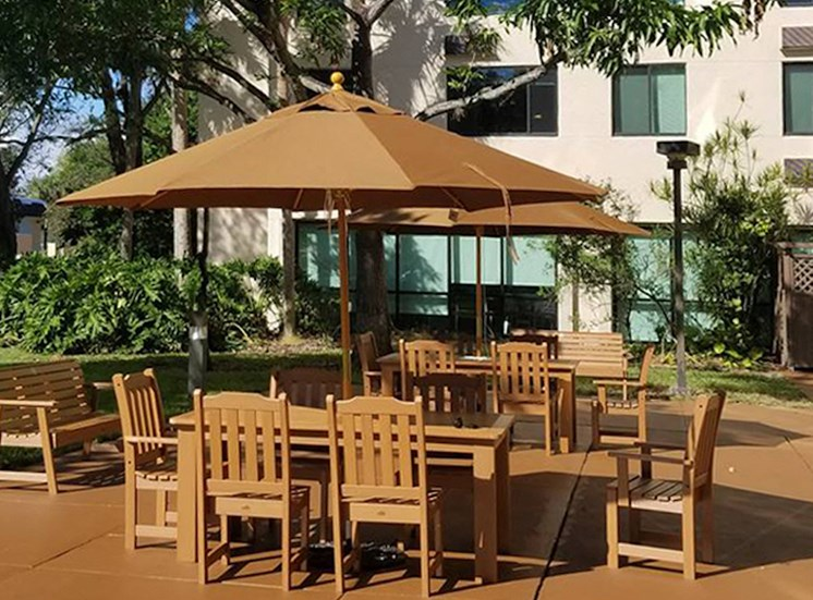 large tables with umbrellas outside at B'nai B'rith I, II, III deerfield apartments in deerfield beach, FL