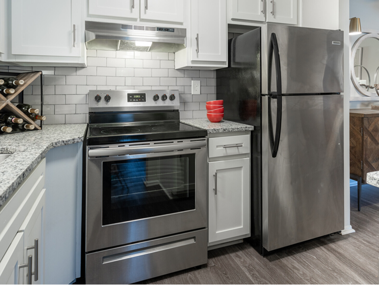 Image of Huron floor plan kitchen with grey plank flooring, stainless steel fridge and stove/oven, and granite counter tops with white cabinets and a partial view into living room