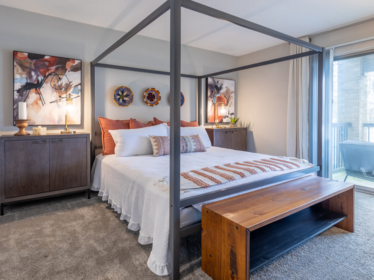 Image of Huron one-bedroom layout with large window/sliding door onto private patio access, plush carpeting, canopy frame bed, and nightstand dressers flanking bed