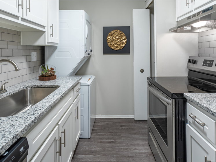 Image of St. Clair two bedroom floor plan Kitchen. Image contains view of Stainless steel oven, brushed finishes on sink, granite counter tops, plank wood flooring, and a washer/dryer in the corner.
