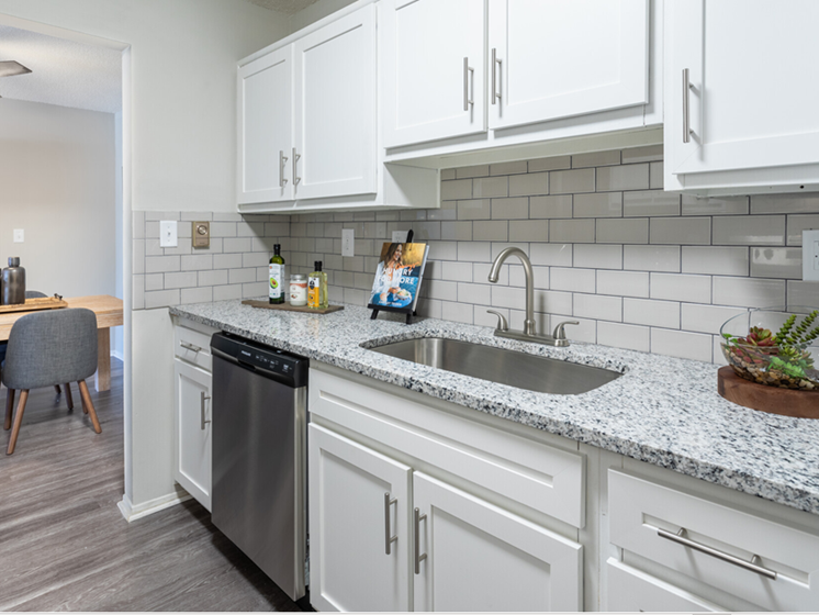 Image of St. Clair two bedroom floor plan kitchen. Image contains view of white cabinetry, tile back splash, granite counter tops, stainless steel dishwasher, and view into dining area