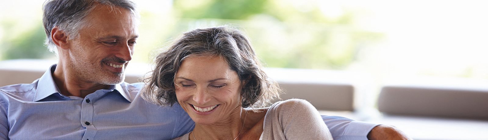 Man looking over woman's shoulder as they both smile and read an electronic device