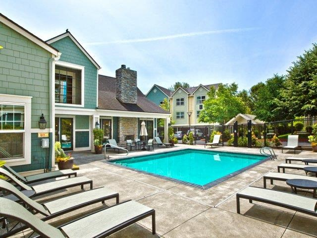 Outdoor pool with lounge chairs and tables with umbrellas