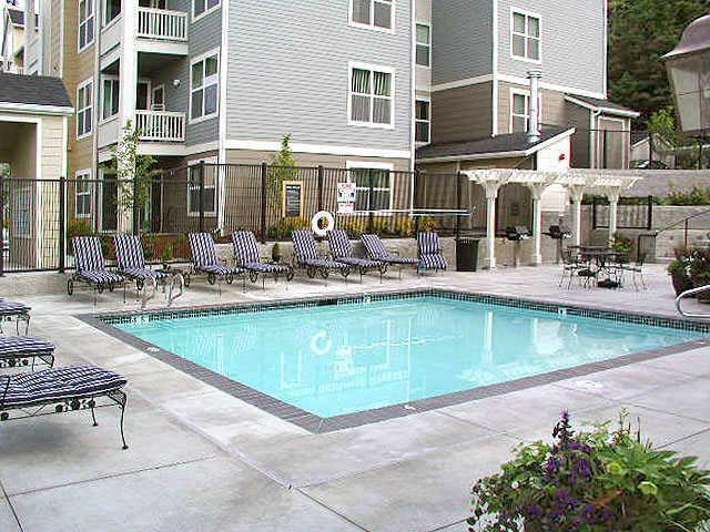 Outdoor pool with lounge chairs, seating areas and barbeque grills