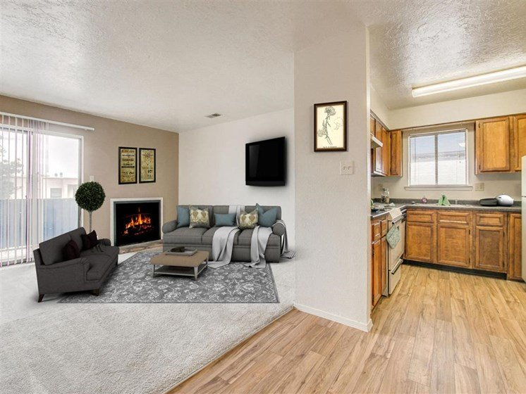 Living room with fireplace and kitchen view Villa La Charles Apartments | Albuquerque NM