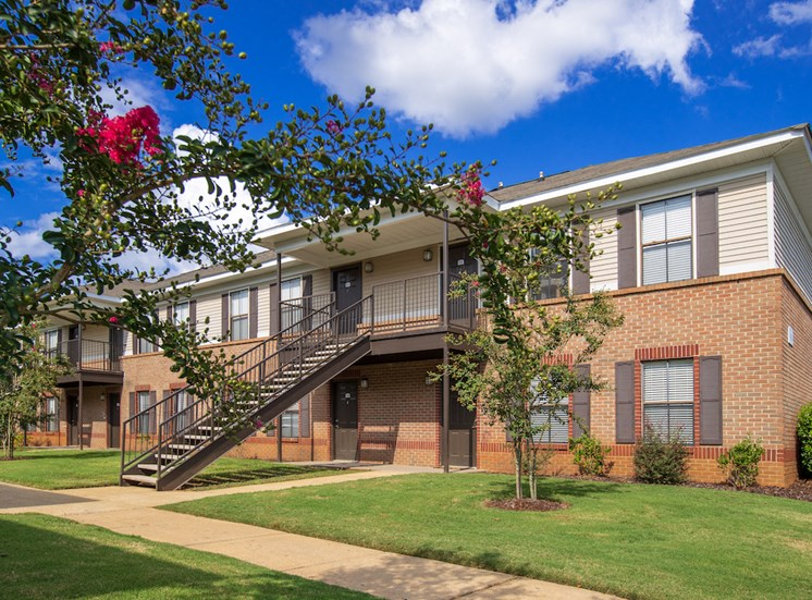 brick apartment building with green grass, sidewalk, and crepe myrtle trees