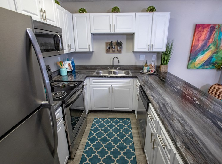 galley kitchen with white cabinets and stainless steel appliances and granite style counters