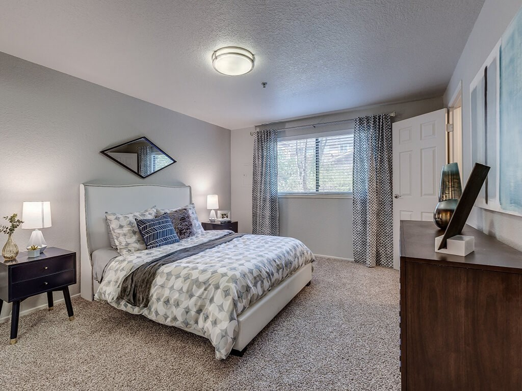 Kent Apartments - Skyview3322 Apartments Carpeted Bedroom With Plush Bedding, Large Window, And Wooden Furnishings