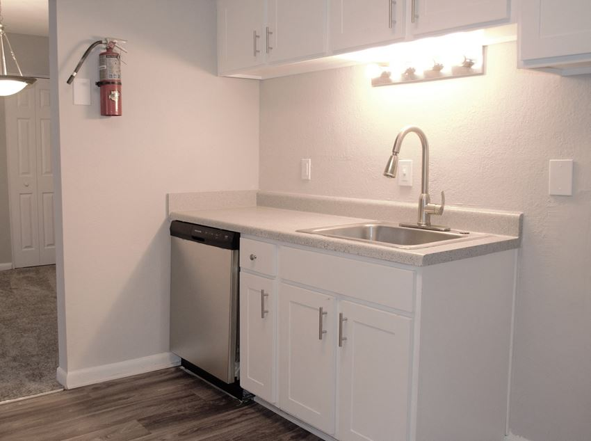 renovated kitchen, white cabinets, stainless steel dishwasher, single sink, grey brown wood style flooring at The Life at Marketplace, Atlanta, Georgia