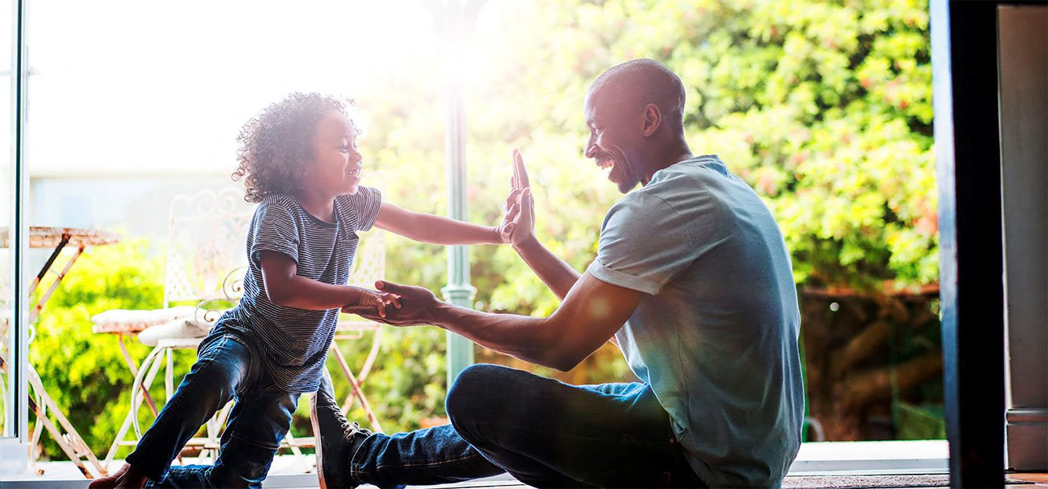 Stock photo of a dad playing with his son at Riverstone Apartments in Antioch, CA