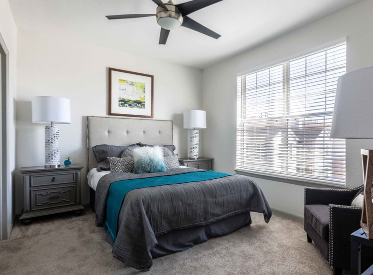 Remington at Lone Tree Master bedroom with beige carpet, queen sized bed and large windows