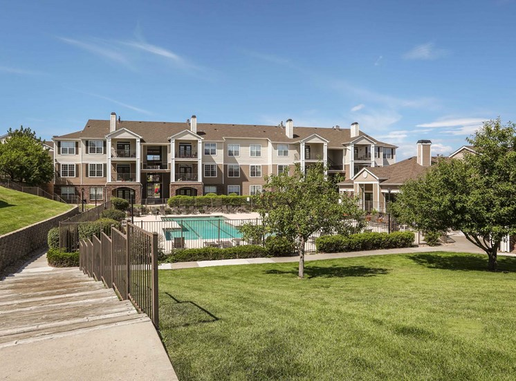 Remington at Lone Tree  grassy hill with stairs down to the pool and more apartments