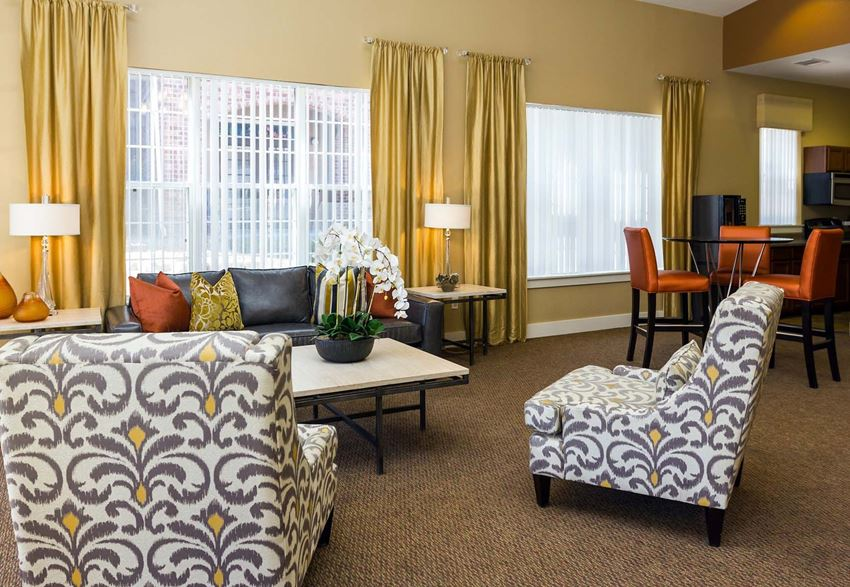 Remington at Lone Tree Clubhouse seating area with grey and yellow patterned chairs, brown carpet and gold drapes around windows