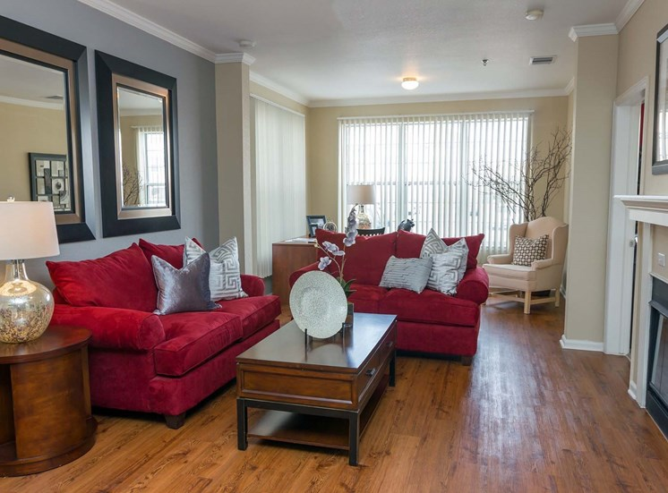 Remington at Lone Tree Living Room with red couches, hardwood-style flooring, and large windows facing outside