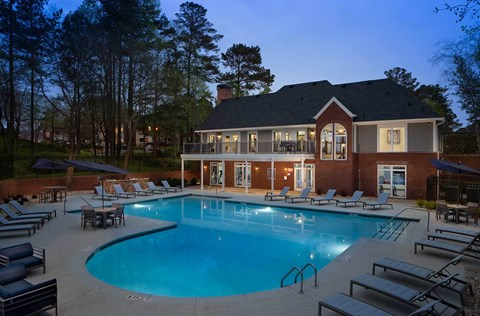 View of the clubhouse at twilight with the pool and sundeck