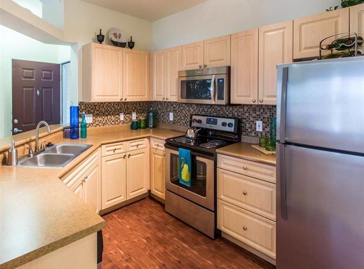 kitchen area with refrigerator, oven, and microwave