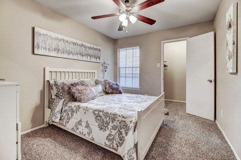 Large bedroom with plush carpet and ceiling fan