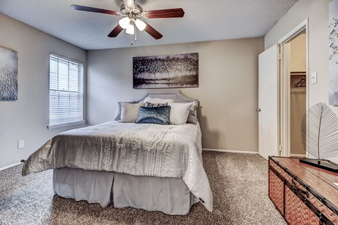 Master bedroom with plush carpet and ceiling fan