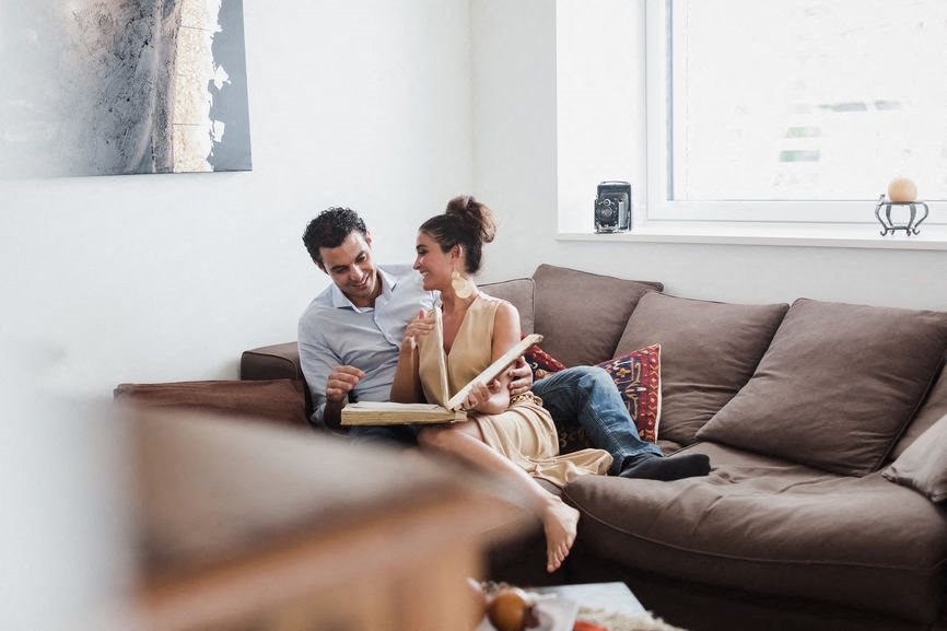 Couple Sitting on Couch Flipping Through Book