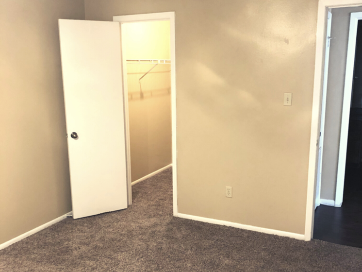 bedroom with neutral brown carpet and white trimming along the wall