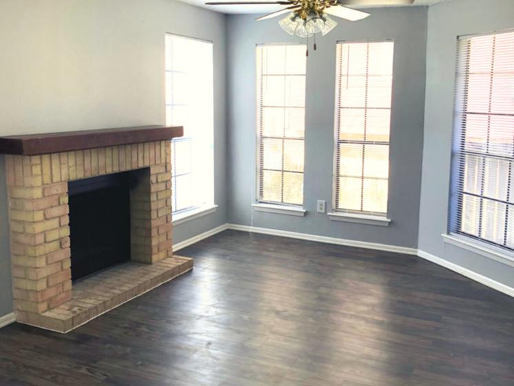 Living room with dark wood flooring and grey walls, 4 wall length windows