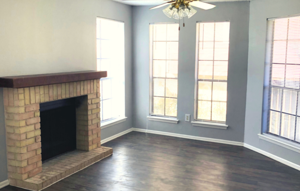 Living room with dark wood floors, brick fireplace with cherrywood mantle, and 4 wall length mirrors