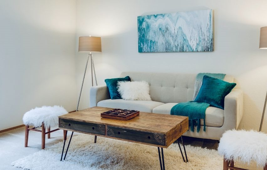 Cream colored couch with blue accents, wooden coffee table, and blue painting hanging on the wall