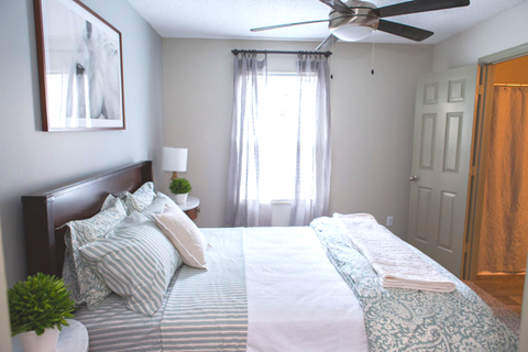 The Southern Apartments Sun-Filled Bedroom with Large Window and Ceiling Fan