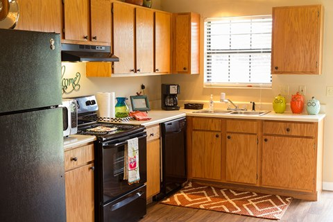 City Edge Flats Equipped Kitchen with Black Appliances, Wood-Style Flooring, and Ample Cabinet Storage