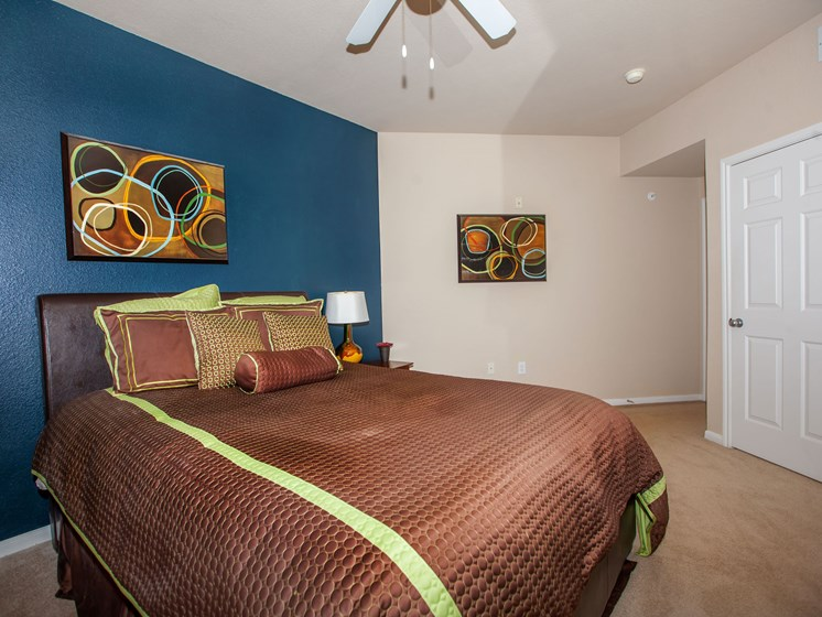 bedroom with brown bedspread and blue wall