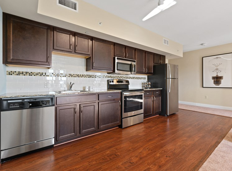Spacious kitchen with stainless steel appliances and wood cabinets at Market Street Flats