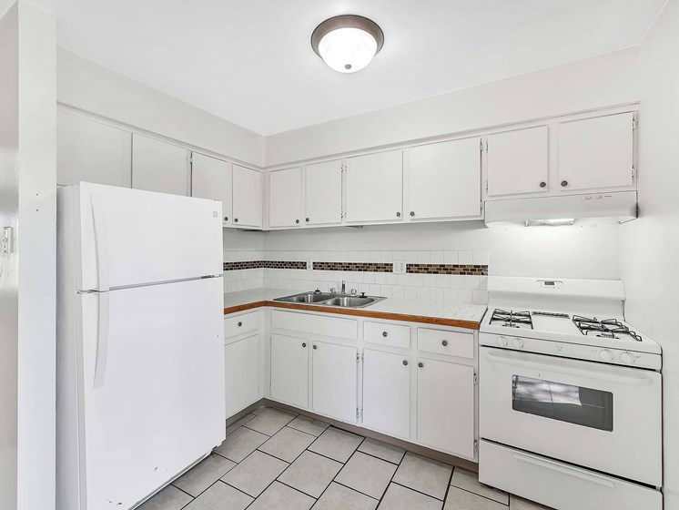 Kitchen With White Cabinetry And Appliances at Rivershell Apartments, Lansing