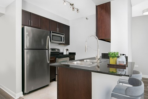 One bedroom kitchen with cherry cabinets, stainless steel appliances, quartz counters, and space for two barstools