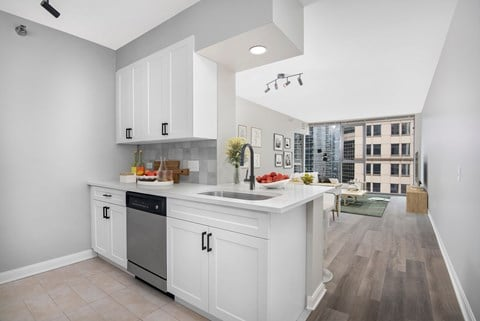 Two bedroom unit kitchen with white cabinets, stainless steel appliances, quartz counters, and hardwood flooring