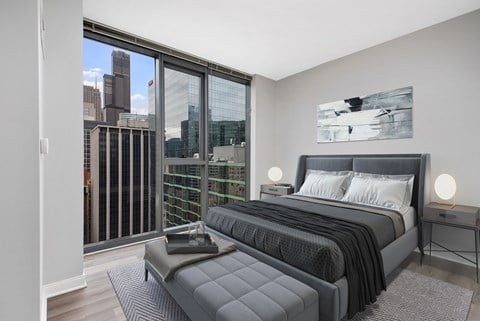 Renovated bedroom with grey walls, floor to ceiling windows, queen sized bed, and hardwood flooring