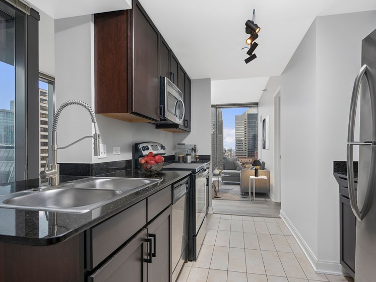 Alleyway kitchen with cherry cabinets, stainless steel appliances, and tile flooring
