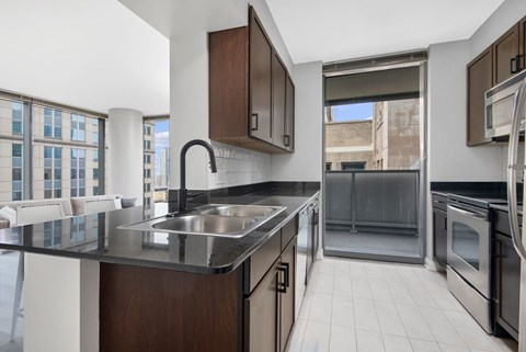 Alleyway kitchen with cherry cabinets, stainless steel appliances, and quartz countertops