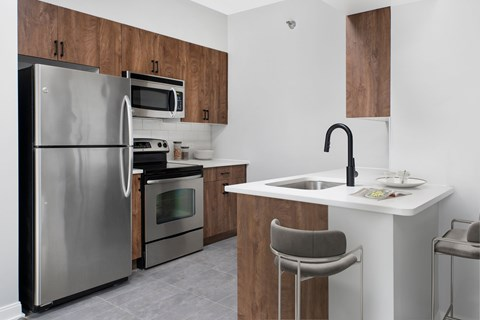 Studio kitchen with cherry cabinets, two barstools, quartz counters and stainless steel appliances